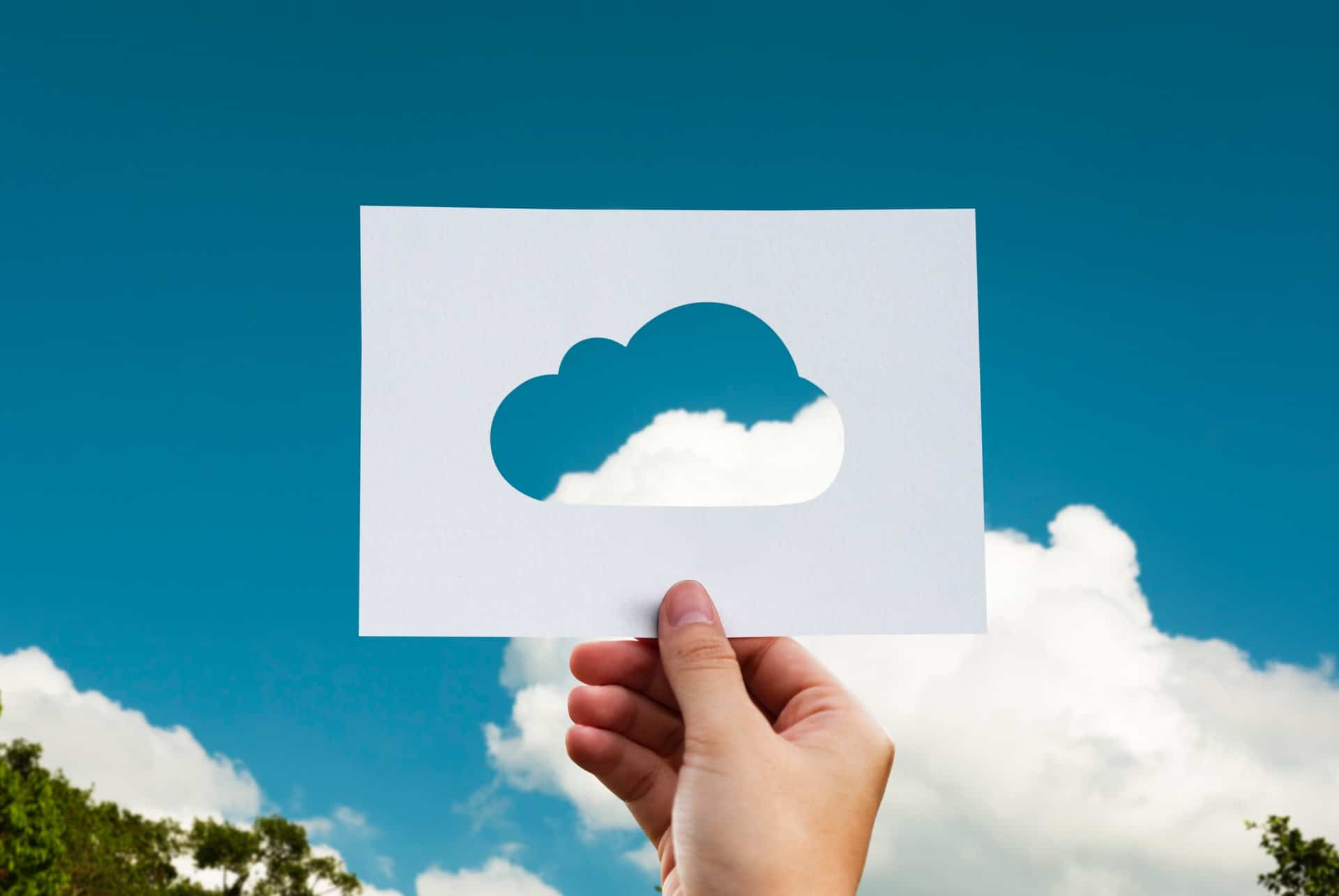 Paper cloud held in front of a blue sky - cloud computing